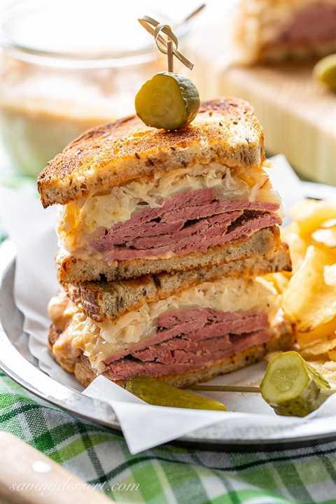 Un sándwich Reuben apilado con pepinillos y servido con papas fritas