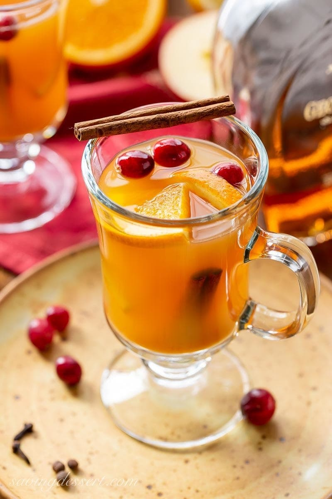 Una taza de sidra de manzana con especias picantes adornada con rodajas de naranja, canela y algunos arándanos frescos