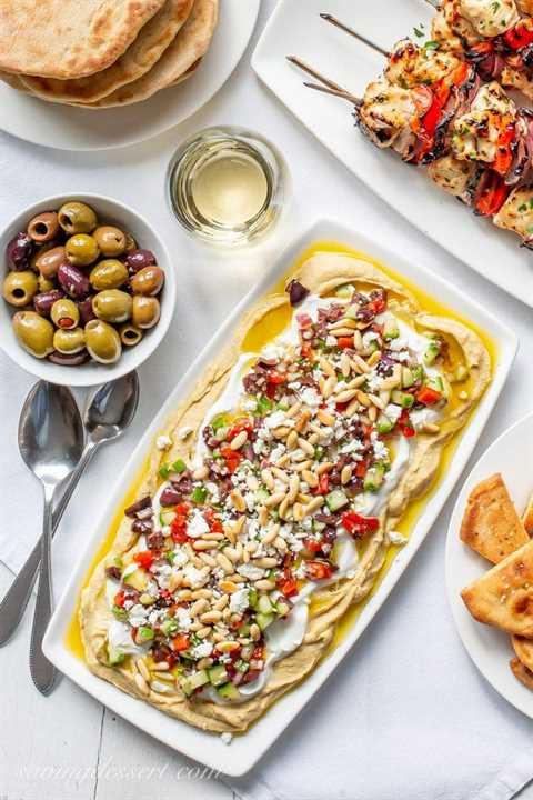 Un plato de salsa griega de hummus, aceitunas, pan de pita fresco y brochetas de pollo marinado en griego