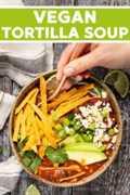 Sopa de tortilla vegana con sabor rico, audaz, tomate, ahumado, lima, ajo y montones de tiras de tortilla al horno crujientes y crujientes. Luego vienen los ingredientes adicionales que realmente sellan el trato. ¡Es rápido y fácil de hacer y totalmente delicioso!