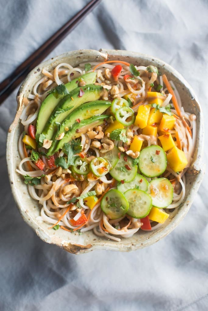 An overhead view of a bowl full of rice, cucumber, mango, bell pepper and avocado noodles.