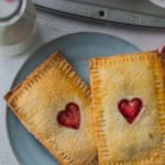 Forget boxed pop tarts, make your own with this recipe for homemade strawberry and cream pop tarts - it has a golden puff pastry crust and a sweet fruity filling with your favorite jam and then topped off with a pinch of sugar cane: the perfect Valentine's Breakfast!