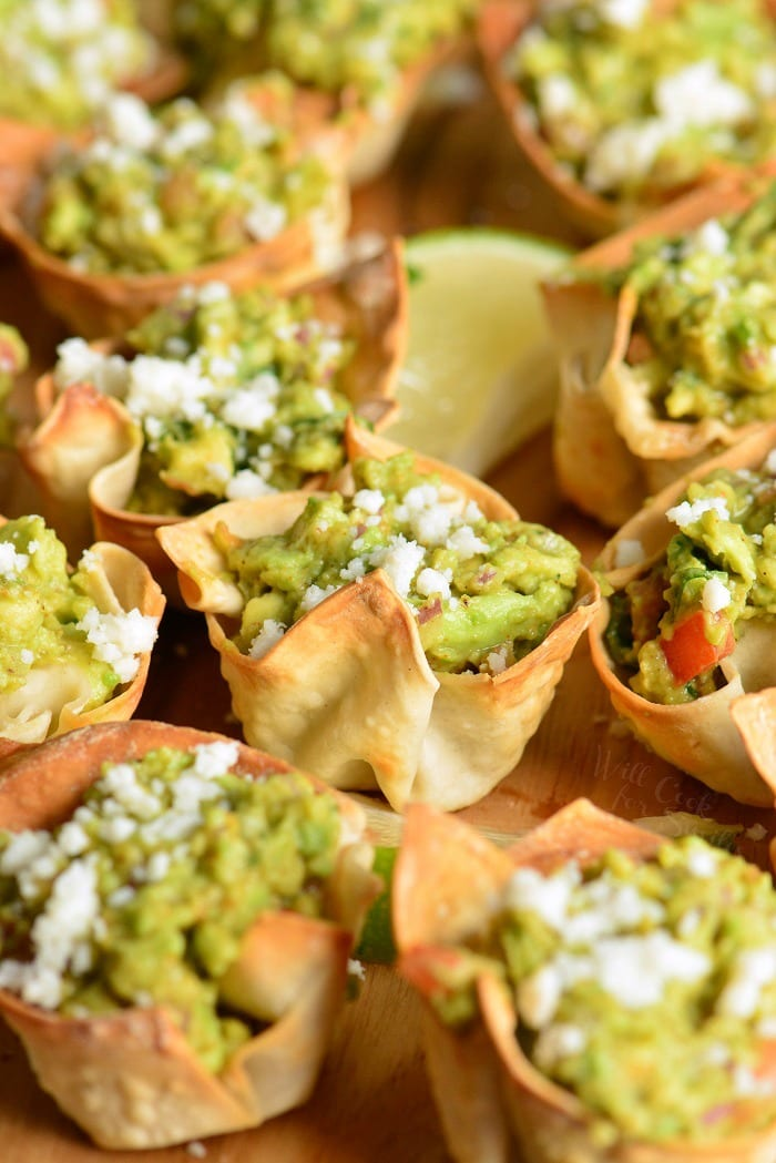 Guacamole in crispy cups. Simple and tasty party snack. They're made with wonton wrappers, stuffed with homemade guacamole, and topped with crumbled Cotija cheese. #appetizer #snack #avocado #guacamole #individual