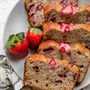Plato de rebanadas de pan de plátano y fresa con fresas frescas en el lateral