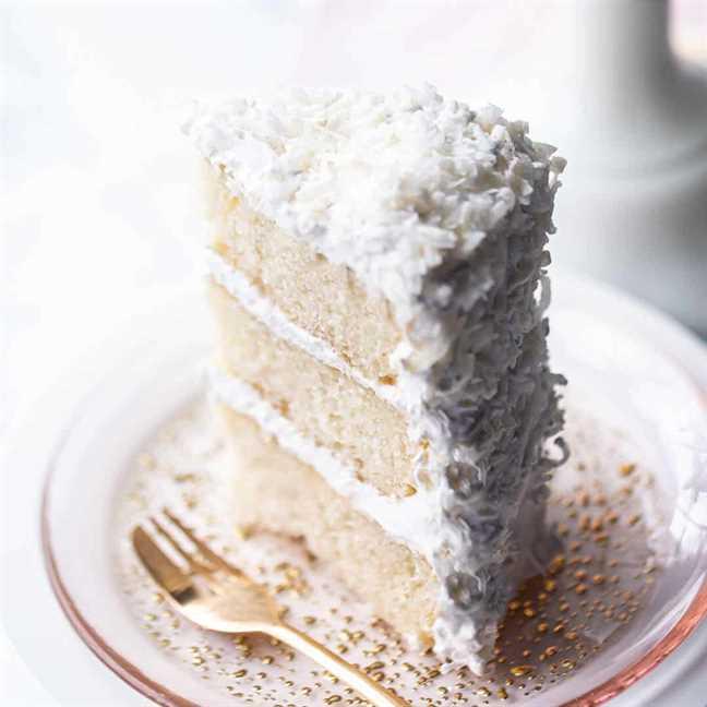 Tall rebanada de pastel de coco en un plato rosa con un tenedor de oro.
