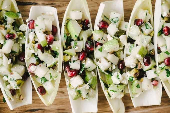 Seis aperitivos rellenos de escarola rellenos de pera, granada y queso azul en una fuente de madera.