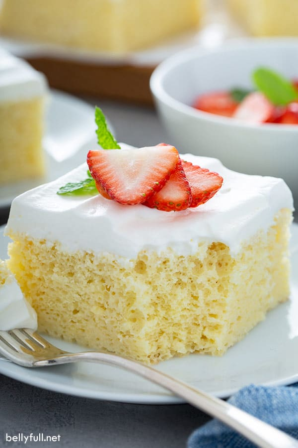 Slice of tres leches cake on a white plate with a fork