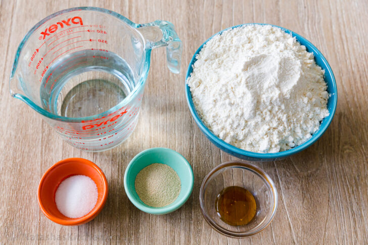 Pizza dough ingredients with warm water, flour, yeast, salt and honey.