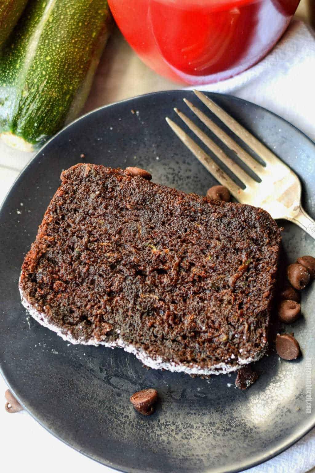 pan de calabacín de chocolate en un plato negro con un tenedor