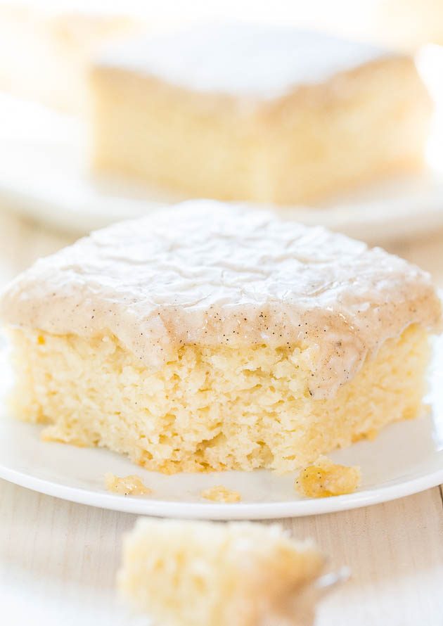 slice of wet vanilla cake with vanilla frosting and missing a bite on a plate