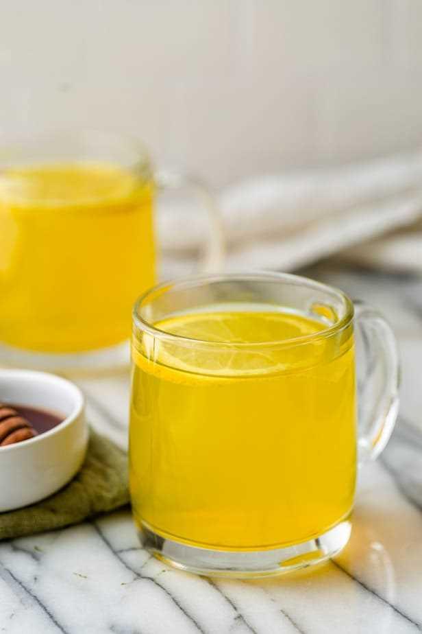 Un vaso de té de cúrcuma de jengibre con una rodaja de limón.