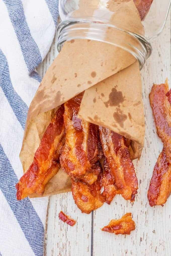 Brown Sugar Bacon envuelto en papel marrón y relleno en un frasco acostado de lado.
