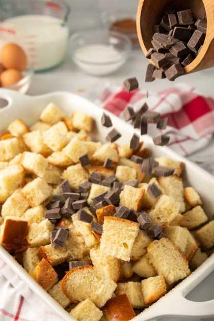 combinando las chispas de chocolate y los cubitos de pan en una cazuela