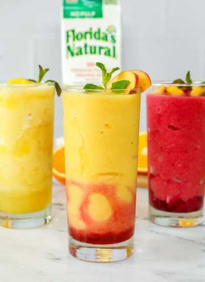 Tres vasos de granizados de jugo de naranja.