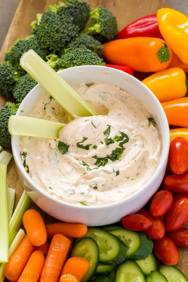 Dip de verduras con apio en el dip y verduras frescas dispuestas.