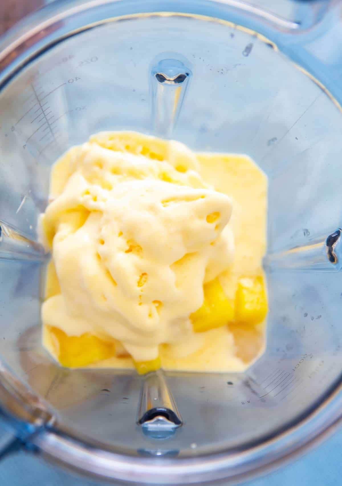 Piña congelada y helado y jugo colocados en una licuadora.