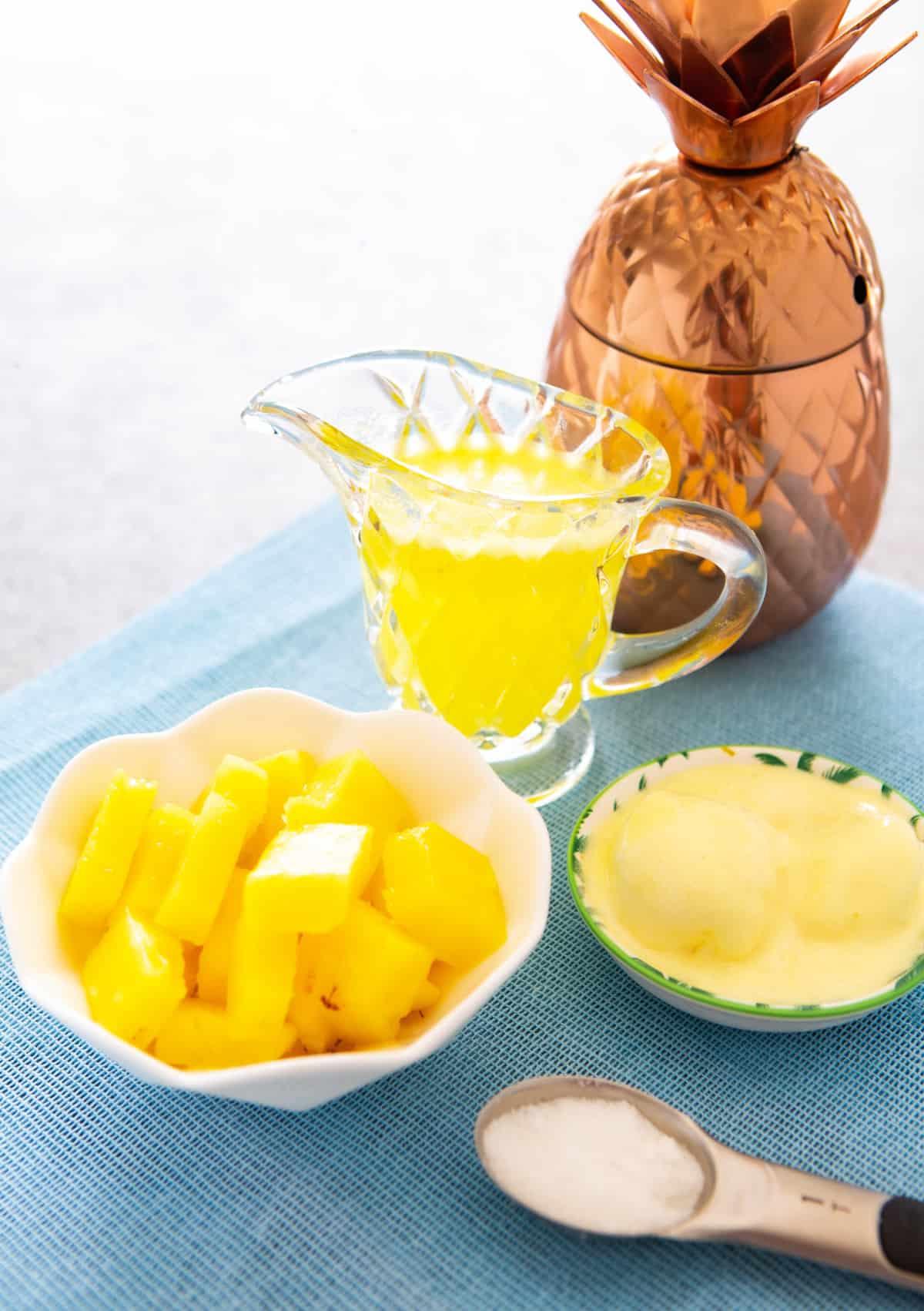 Piña congelada en un bol, jugo en una jarra y helado de vainilla, todo sobre una mesa.