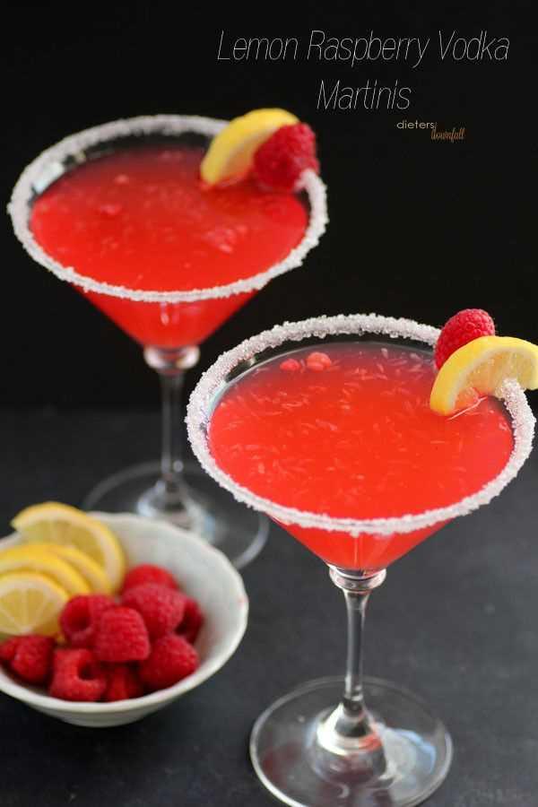 Martinis de vodka de limón y frambuesa con un tazón de rodajas de limón fresco y frambuesas.