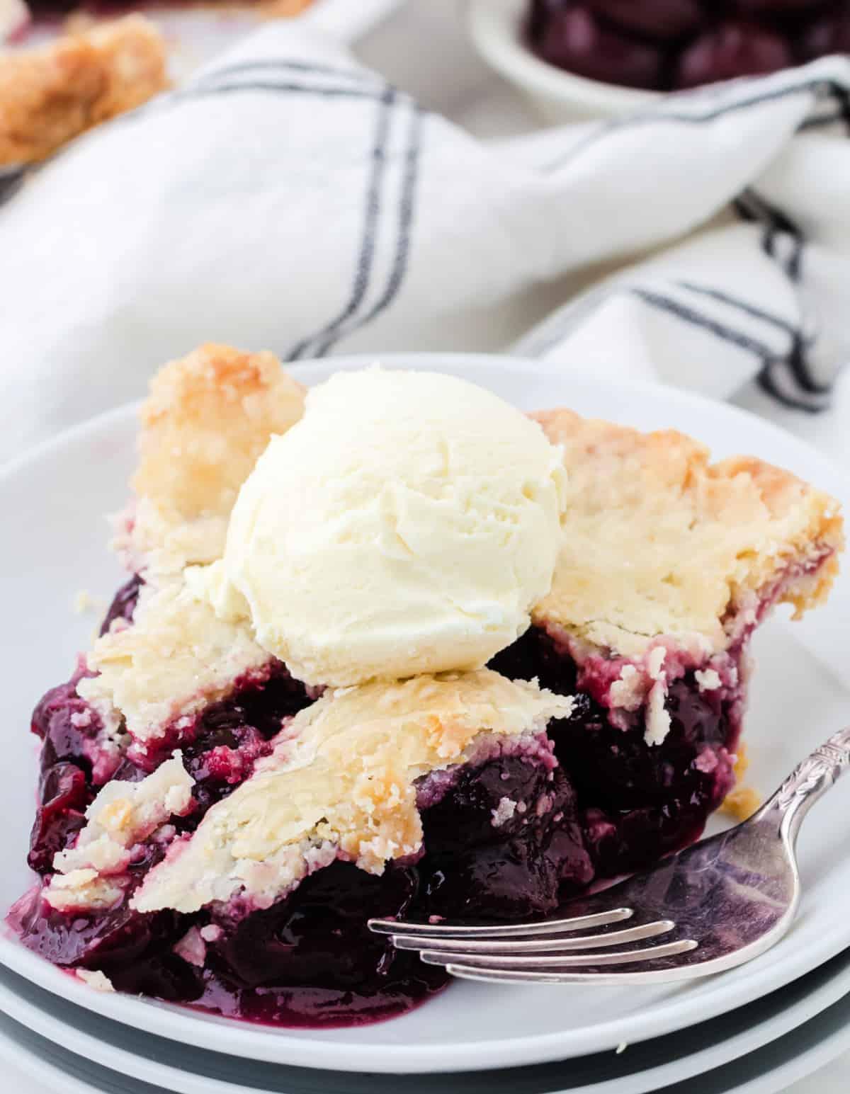Una rebanada de pastel de cerezas en un plato blanco con una bola de helado de vainilla.