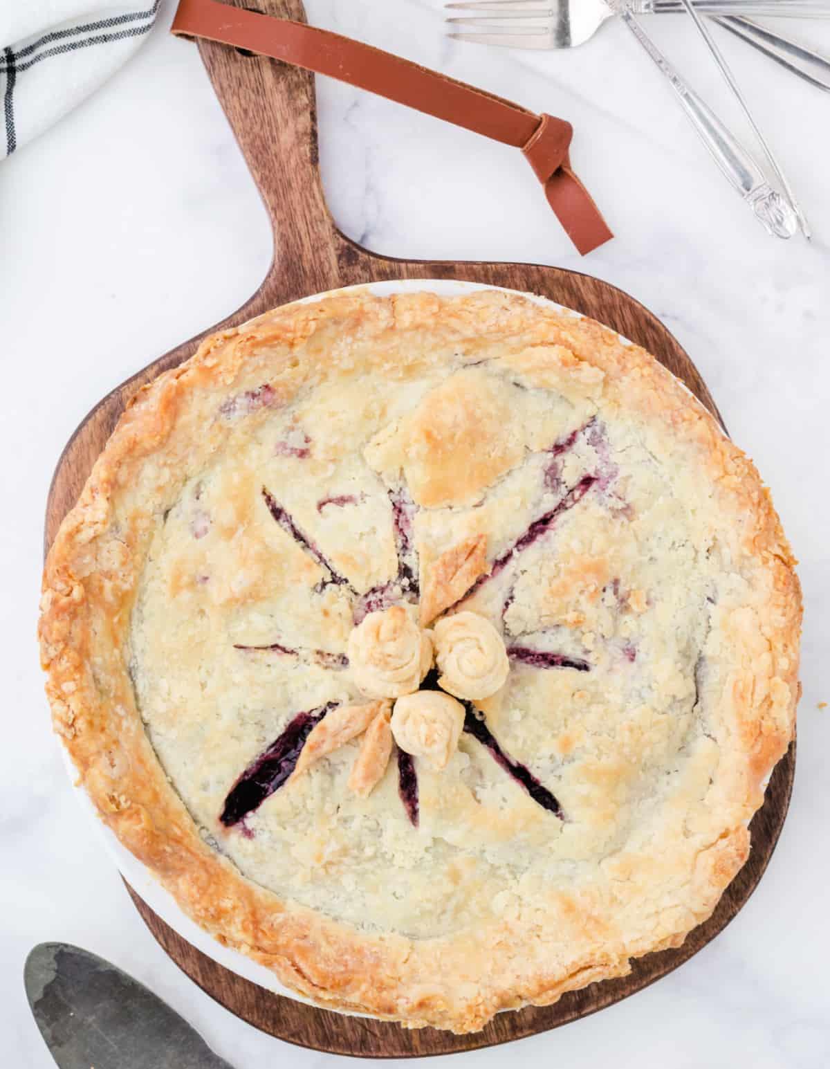 Un pastel de cerezas entero sobre una pequeña tabla de cortar de madera.