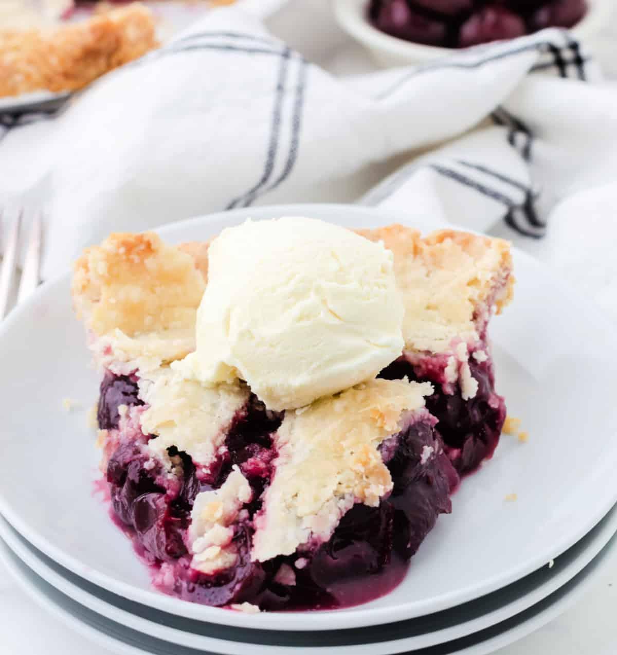 Un trozo de tarta de cerezas en un plato blanco.
