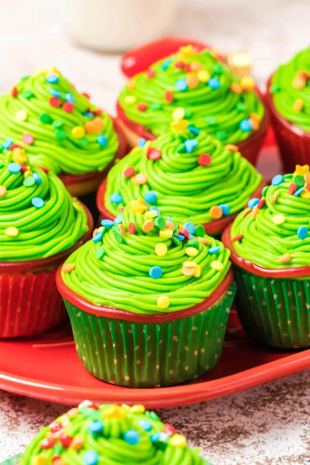 Siete cupcakes de árbol de Navidad en un plato rojo.
