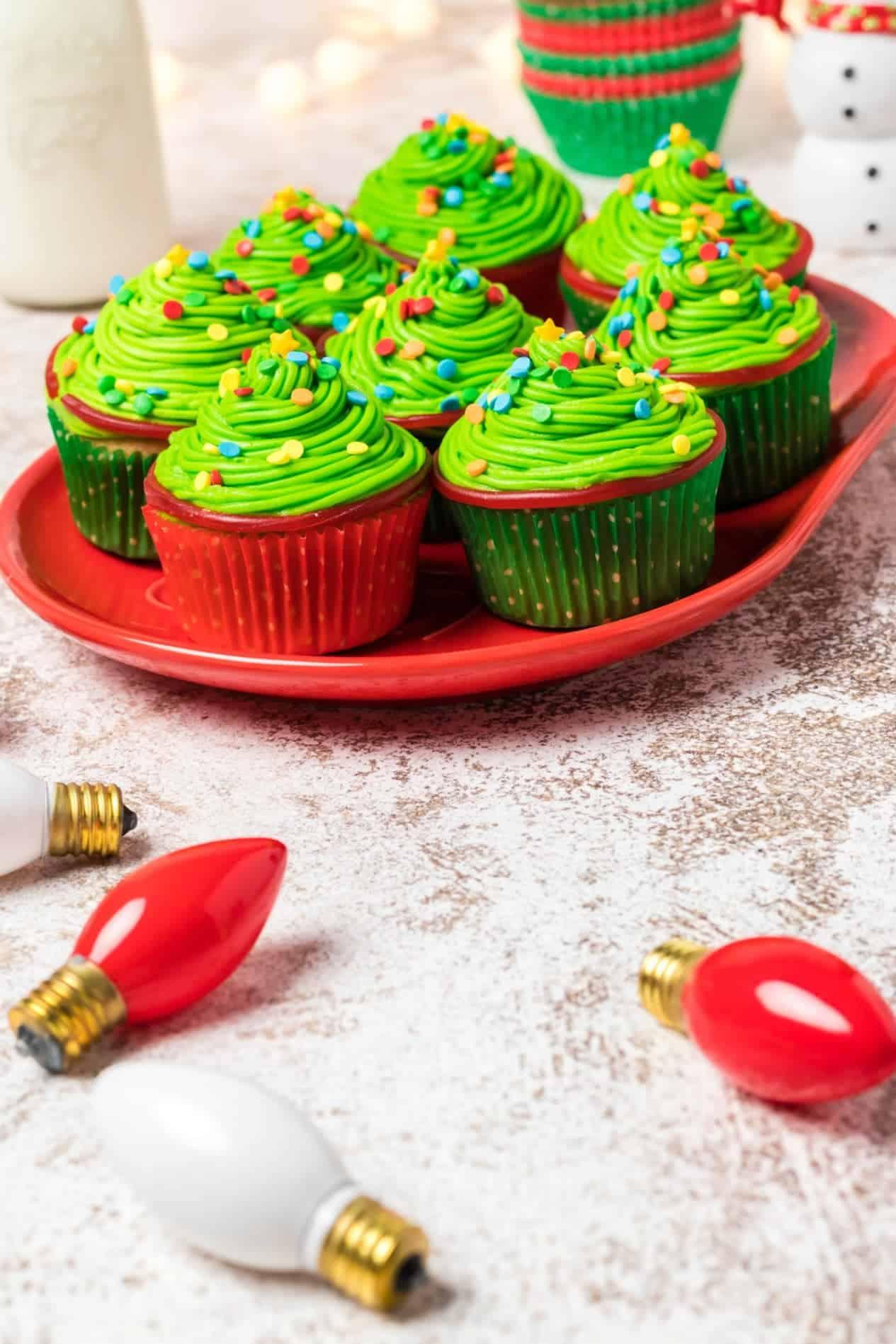 Cupcakes de árbol de Navidad en un plato rojo con luces de Navidad esparcidas alrededor.
