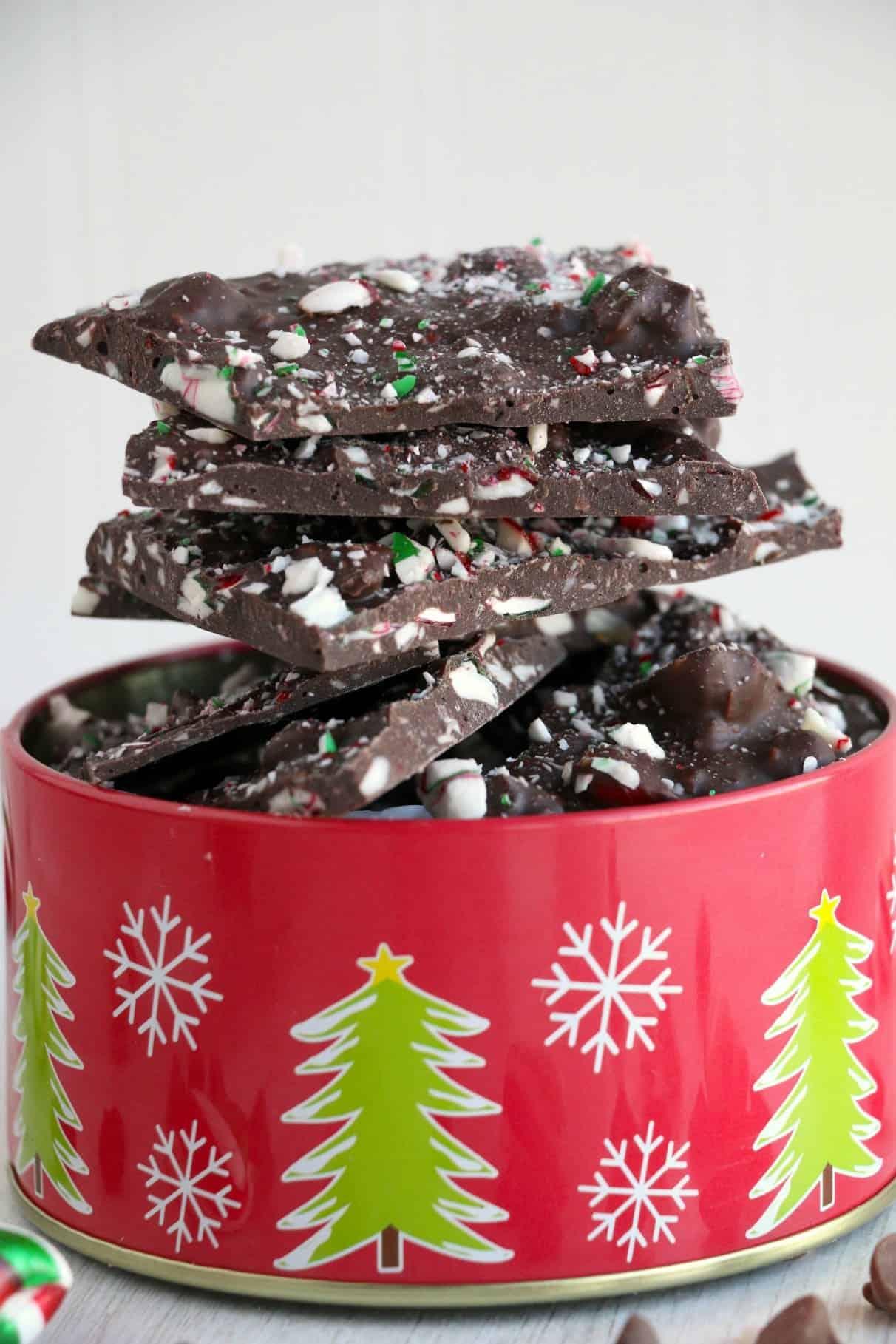 Corteza de chocolate y menta apiladas una encima de la otra en una lata navideña.