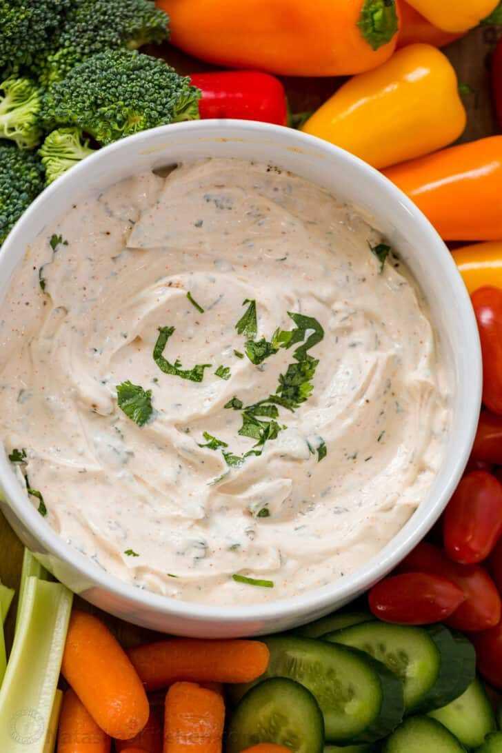 Dip de verduras en un plato adornado con cilantro con verduras frescas dispuestas.